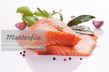 Filet de saumon cru avec les herbes, l'ail et le poivre en grains