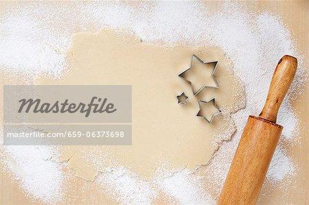 Sugar Cookie-Teig mit Ausstechformen Stern und einem Nudelholz ausgerollt