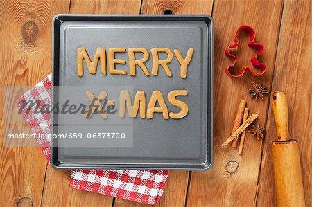 Schneiden Sie die Worte Frohe Weihnachten von Plätzchenteig