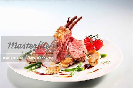 Couronne d'agneau aux champignons, haricots et tomates cerises