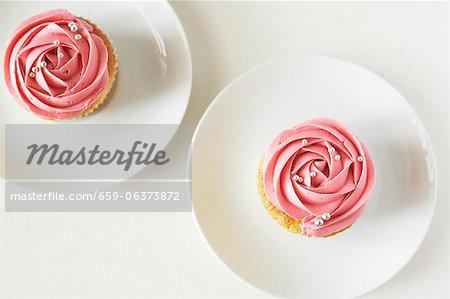 Zwei kleine Kuchen verziert mit Erdbeer Sahne und Silber-Kugeln