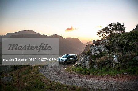Véhicule sur piste de montagne au coucher de soleil, Table Mountain National Park, Cape Town, Western Cape, Afrique du Sud