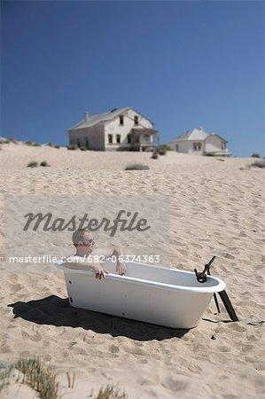 Man sitting in victorian bathtub on sand dune, Kolmanskop, Luderitz, Karas Region, Namibia