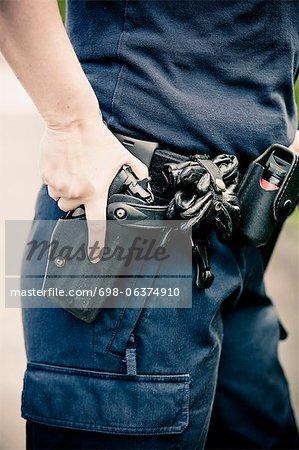Partie centrale d'un policier de port de ceinture de matériel avec la main sur les armes à feu