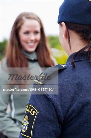 Femme heureuse femme policier en regardant