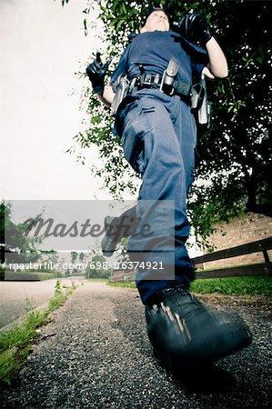 Vue d'angle faible d'une femme officier de police en cours d'exécution