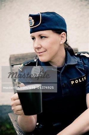 Jeune femme policier tenant la tasse à café