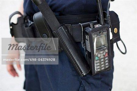Partie centrale d'un policier avec un bâton walkie-talkie et nuit sur la ceinture de l'équipement