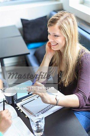 Glückliche junge Frau sitzend mit Buch am Tisch in der Mensa der Universität