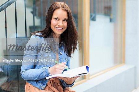 Porträt einer glücklich junge Studentin mit Buch und Stift
