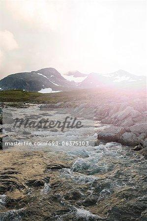 Stream und Felsen von Schnee bedeckt Berg