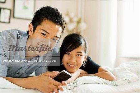 Portrait d'un couple d'adolescents heureux couché dans son lit