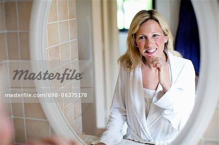 Frau mittleren Alters, putzen ihre Zähne im Spiegel
