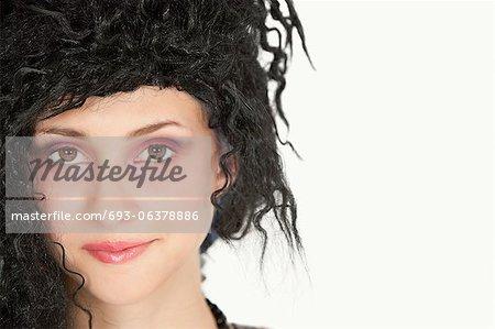 Portrait en gros plan d'une belle jeune femme avec les cheveux taquiné sur fond gris