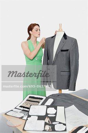 Concepteur femelle réglage manteau sur mannequin de couture sur fond gris
