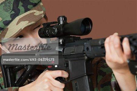 Jeune femme soldat US Marine Corps avec fusil d'assaut M4 à fond marron