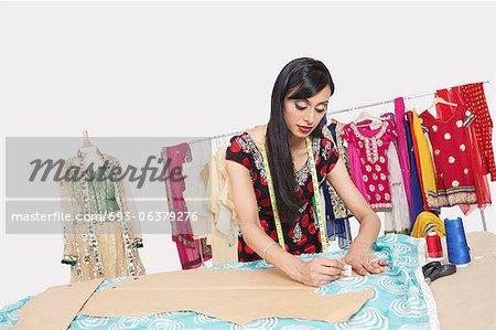 Designer de vêtements femme indienne travaille dans le studio de design
