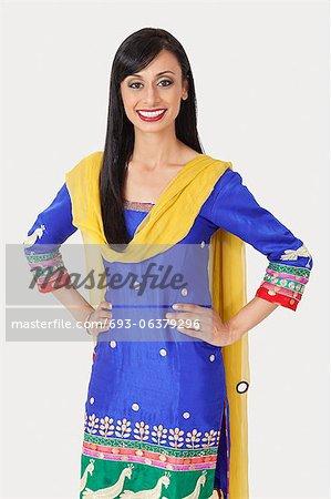 Porträt von ziemlich indische Frau in traditioneller Kleidung stehend mit den Händen an den Hüften über den grauen Hintergrund
