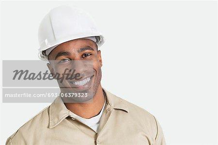 Portrait de joyeux construction africaine au fil avec casque de sécurité sur fond gris