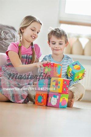 Empiler les blocs tout en étant assis sur le plancher des enfants
