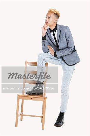 Gentil garçon adolescent debout avec un pied sur une chaise sur fond gris