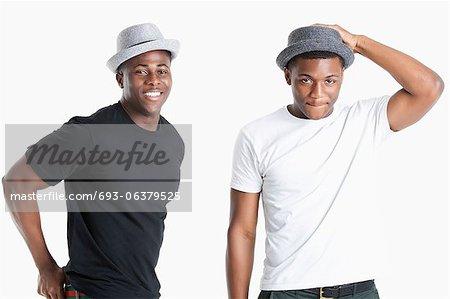 Portrait de heureux jeunes hommes afro-américains portant des chapeaux sur fond gris