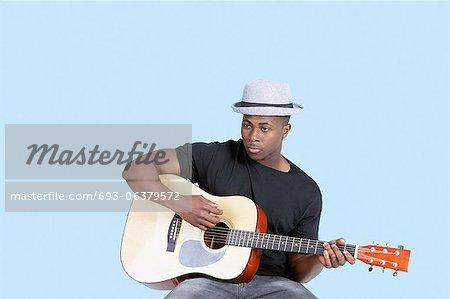 Young African American man jouer de la guitare sur fond bleu clair