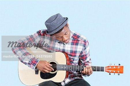 Jeune homme coiffé comme il joue de la guitare sur fond bleu clair