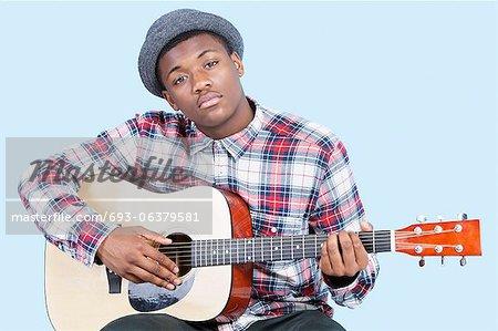 Portrait d'un jeune homme jouer de la guitare sur fond bleu clair