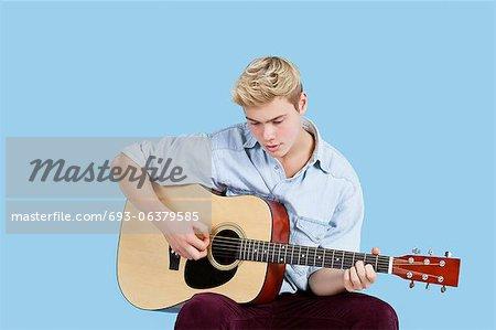 Jeune homme jouer de la guitare sur fond bleu