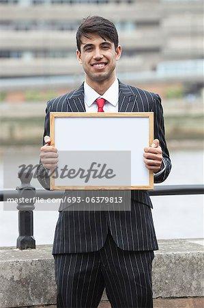 Portrait de jeune homme d'affaires indien, tenant une pancarte blanche