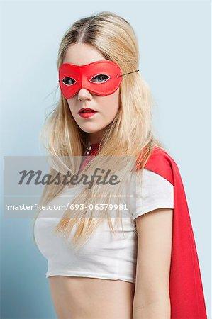 Portrait de jeune femme portant le costume de super héros sur fond bleu