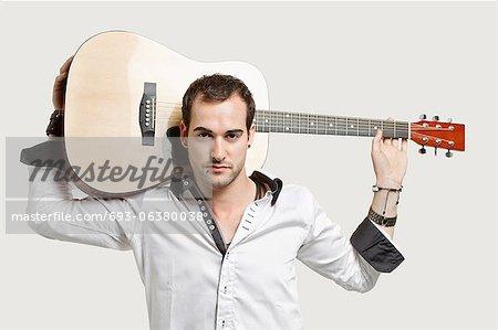 Portrait de jeune homme transportant guitare par-dessus son épaule sur fond gris