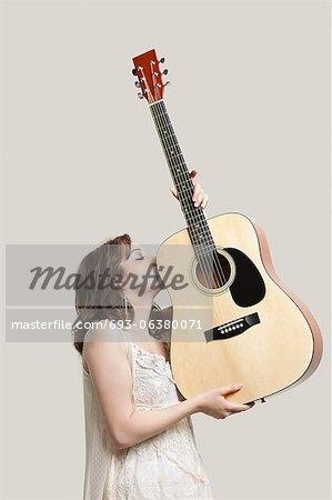 Jeune femme embrasse guitare sur fond gris