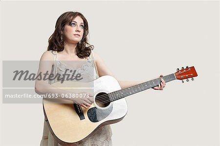 Jeune femme regardant vers le haut tout en jouant la guitare sur fond gris