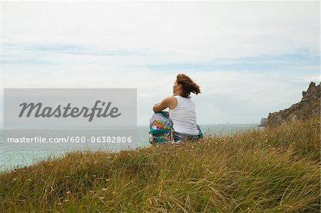 Frau sitzen und schauen in die Ferne, am Strand, Camaret-Sur-Mer, Halbinsel Crozon, Finistere, Bretagne, Frankreich