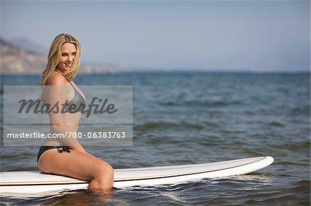 Surfer Sitting on Surfboard