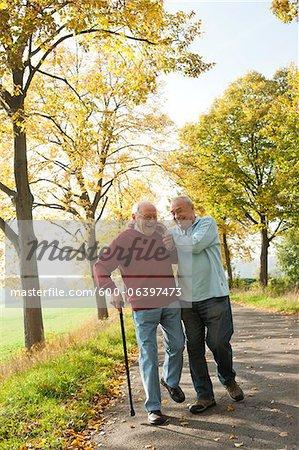 Seniors hommes marchant sur le chemin bordé d'arbres en automne, Lampertheim, Hesse, Allemagne