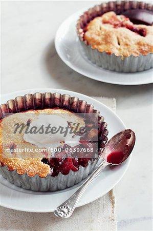 Tartelettes de prune avec crème glacée sur les plaques avec des cuillères