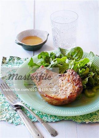 Côtelette de porc et de la salade sur une assiette avec une fourchette et couteau sur napperon