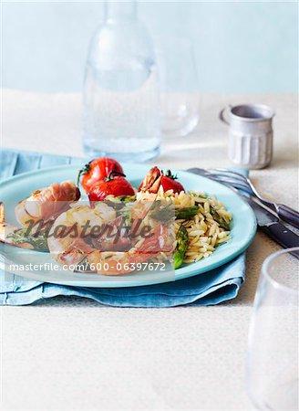 Prosciutto enveloppé de crevettes avec Orzo et asperges et tomates