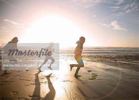 Famille courir ensemble sur la plage
