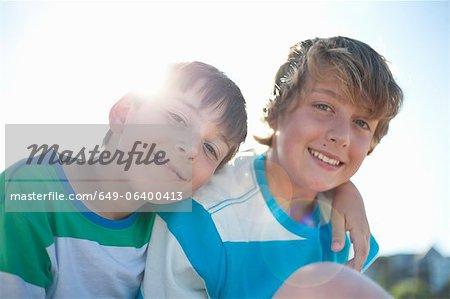 Frères souriants s'enlaçant à l'extérieur