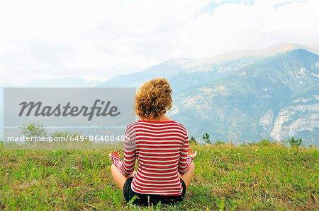 Femme méditant sur colline rurale