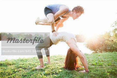 Couple practicing yoga in garden