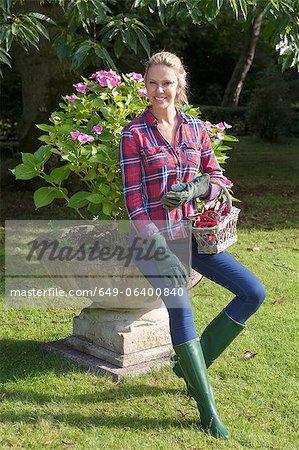 Woman carrying flowerpot in garden