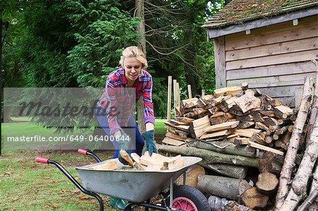 Woman loading firewood into wheelbarrow
