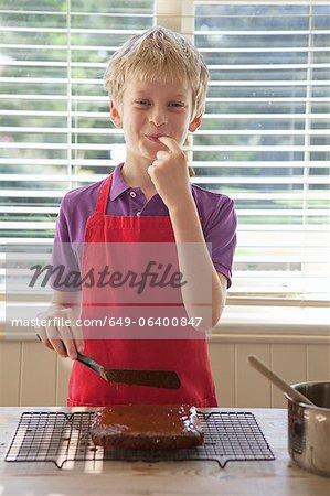 Junge Verkostung Kuchen Glasur in Küche