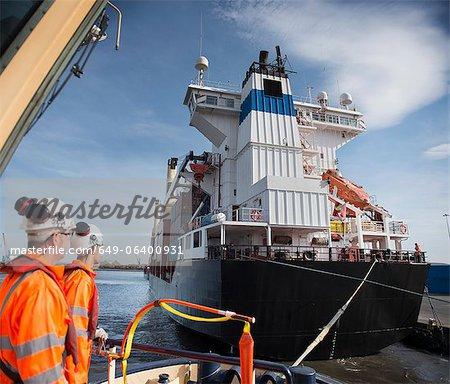 Arbeitnehmer auf Schlepper Boot mit Blick auf Schiff