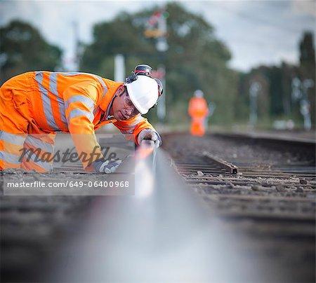 Cheminot examinant la voie ferrée